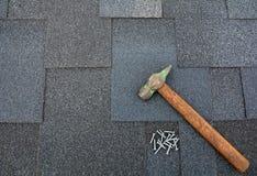 Feche acima da vista no fundo das telhas do telhado de asfalto com martelo e pregos Fotos de Stock