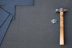 Feche acima da vista no fundo inacabado das telhas do telhado de asfalto com martelo e pregos Fotos de Stock