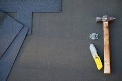 Feche acima da vista no fundo inacabado das telhas do telhado de asfalto com martelo e pregos A instalação do revestimento waterp Fotos de Stock