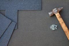 Feche acima da vista no fundo inacabado das telhas do telhado de asfalto com martelo e pregos A instalação do revestimento waterp Fotografia de Stock Royalty Free