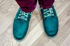 Feche acima da vista nos pés do ` s do homem em calças de brim escuras e nas botas de couro Imagem de Stock