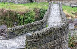 Feche acima da vista da ponte de pedra histórica das épocas romanas em um vale isolado da montanha imagens de stock royalty free