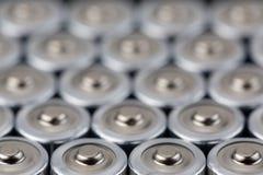 Feche acima da vista superior em fileiras borradas do fundo do sumário da energia das baterias do AA das baterias Fotografia de Stock