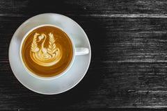 Feche acima da xícara de café branca, latte com arte do latte no fundo de madeira preto Imagens de Stock