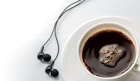 Feche acima da xícara de café com o fone de ouvido no branco Foto de Stock Royalty Free
