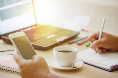 Feche acima da xícara de café e do laptop com mão do homem de negócio que usa o telefone esperto Foto de Stock