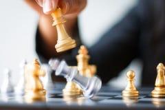 Feche acima da xadrez dourada do tiro para derrotar a xadrez de prata o do rei da matança Fotografia de Stock