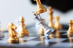 Feche acima da xadrez dourada do tiro para derrotar a xadrez de prata o do rei da matança Imagens de Stock