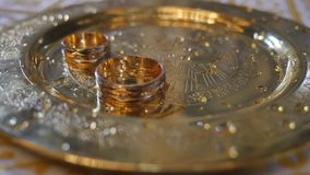 Feche acima das alianças de casamento dos recém-casados durante a consagração da água santamente na igreja antes da cerimônia de  vídeos de arquivo