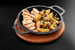 Feche acima das batatas fritadas com o peito de frango do cogumelo na frigideira na grade preta do restaurante do menu do fundo fotos de stock royalty free
