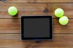 Feche acima das bolas de tênis e do PC da tabuleta na madeira Imagem de Stock