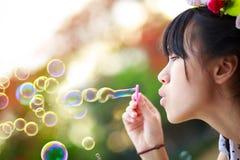 Feche acima das bolhas de sabão de sopro da menina do adolescente foto de stock royalty free