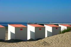 Feche acima das cabines da praia com o cais no fundo Foto de Stock Royalty Free