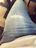 Feche acima das calças de brim rasgadas foto de stock royalty free
