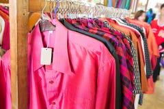 Feche acima das camisas coloridas feitas da seda no trilho de suspensão Fotos de Stock Royalty Free