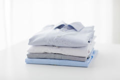 Feche acima das camisas passadas e dobradas na tabela Fotografia de Stock Royalty Free