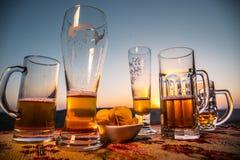 Feche acima das canecas vazias de cerveja em um fundo do nascer do sol com montanhas O partido da cerveja está sobre o conceito fotos de stock