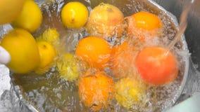 Feche acima das citrinas que caem em uma água vídeos de arquivo