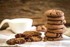 Feche acima das cookies empilhadas dos pedaços de chocolate no guardanapo com b de madeira Foto de Stock Royalty Free