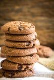 Feche acima das cookies empilhadas dos pedaços de chocolate no guardanapo com b de madeira Imagens de Stock