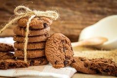 Feche acima das cookies empilhadas dos pedaços de chocolate no guardanapo com b de madeira Fotos de Stock