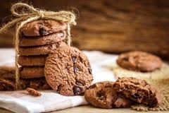 Feche acima das cookies empilhadas dos pedaços de chocolate no guardanapo com b de madeira Fotografia de Stock