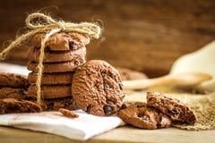 Feche acima das cookies empilhadas dos pedaços de chocolate no guardanapo com b de madeira Foto de Stock