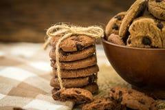 Feche acima das cookies empilhadas dos pedaços de chocolate no guardanapo com b de madeira Fotografia de Stock Royalty Free