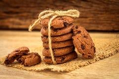 Feche acima das cookies empilhadas dos pedaços de chocolate no guardanapo com b de madeira Imagem de Stock Royalty Free