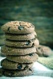 Feche acima das cookies empilhadas dos pedaços de chocolate no guardanapo com de madeira Fotos de Stock Royalty Free