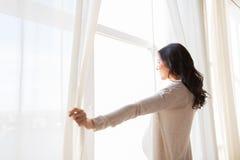 Feche acima das cortinas de janela da abertura da mulher gravida Foto de Stock