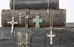 Feche acima das cruzes antigas e modernas nas Bíblias de couro antigas Imagem de Stock Royalty Free