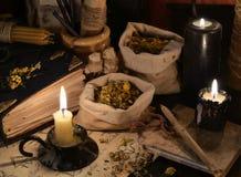 Feche acima das ervas curas, dos papéis da alquimia e das velas ardentes Imagens de Stock Royalty Free