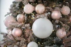 Feche acima das esferas que são ficadas situadas em um abeto e em umas faíscas amarelas pequenas da festão incluída foto de stock royalty free