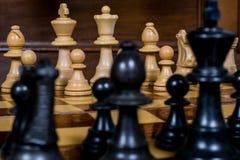 Feche acima das estatuetas brancas e pretas da xadrez em uma placa de xadrez Fotos de Stock