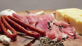 Feche acima das fatias finas de prosciutto com as salsichas cruas secas e queijo suíço na placa de corte de madeira vídeos de arquivo
