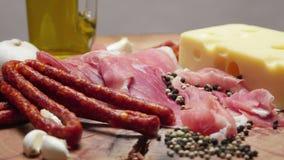 Feche acima das fatias finas de prosciutto com as salsichas cruas secas e queijo suíço na placa de corte de madeira filme