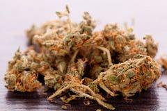 Feche acima das folhas secadas da marijuana na tabela Imagens de Stock Royalty Free