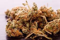 Feche acima das folhas secadas da marijuana na tabela Imagem de Stock Royalty Free