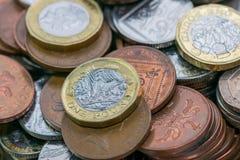 Feche acima das fotos do foco da moeda de libra nova de Reino Unido, entre outras moedas britânicas fotografia de stock