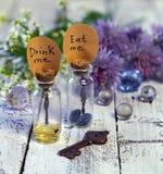 Feche acima das garrafas bonitos com etiquetas comem-me e bebem-nos me, a chave, as bolas de cristal e as flores Fotografia de Stock
