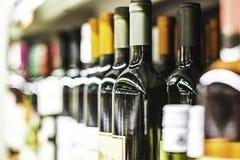 Feche acima das garrafas de vinho na prateleira na loja imagem de stock royalty free