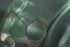 Feche acima das gotas do óleo que flutuam na superfície da água Fotografia de Stock Royalty Free