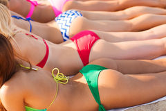Feche acima das jovens mulheres que encontram-se na praia Imagens de Stock Royalty Free