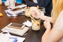 Feche acima das jovens senhoras colhidas que comem o granola e que falam e que discutem negócios durante seu café da manhã do neg Imagens de Stock Royalty Free