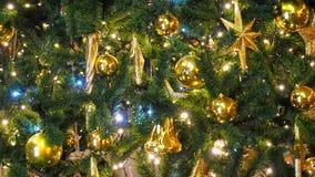 Feche acima das luzes de uma árvore de Natal que brilham na noite com fora de fundo do foco Árvore do ano novo com decorações e filme