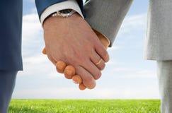 Feche acima das mãos alegres masculinas com alianças de casamento sobre Imagens de Stock Royalty Free