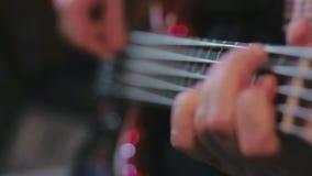 Feche acima das mãos baixas do guitarrista que jogam a guitarra vídeos de arquivo