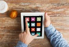 Feche acima das mãos com ícones do menu no PC da tabuleta Imagens de Stock