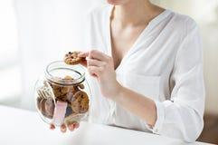Feche acima das mãos com as cookies do chocolate no frasco Fotos de Stock Royalty Free